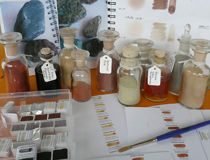 Bottles of pigment and workbook pages