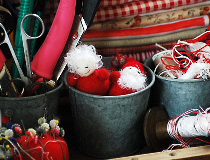 Folded fabric, spools of threads and tins of scissors in Mel's Natale studio.