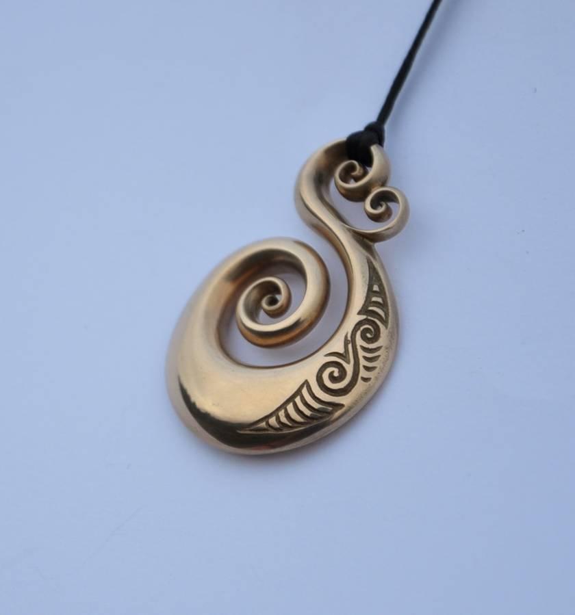 Solid Bronze Koru Pendant on black adjustable cord.