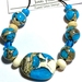 One large flat bead accent central bead with small spacer beads and six medium sized beads.