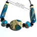 One large flat bead accent central bead with eight small spacer beads and two beautiful long beads.