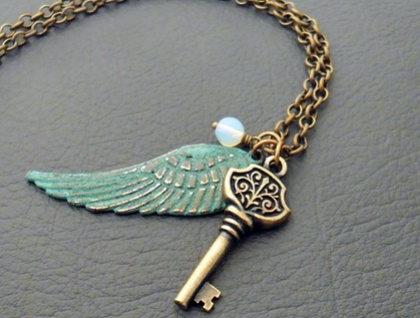 Angyalka necklace: angel-wing pendant with verdigris patina, key charm, and antique moonstone glass