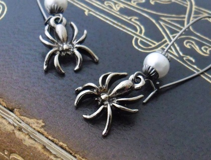 Spider Egg-Sac earrings: shiny dark-grey spider charms with white glass pearls on long ear-wires