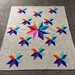 Wonderful handmade crochet blanket, Carpinter's Wheel design - stars in rainbow colours, textured.