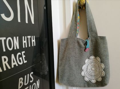 gray blanket bag with doily and funky floral lining