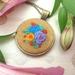 Miniature hand embroidered pendant