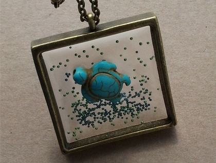 Resin pendant with Turquoise turtle and micro beads on chain.