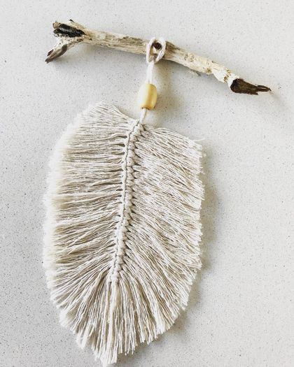 Macrame feather wall hanging on driftwood
