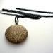 Patterned brass locket necklace on long black chain