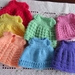 7 small knitted dolls dresses. 1 for each day of the week.