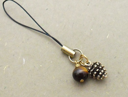 Tiger Pinecone cellphone charm with golden pinecone, striped brown tiger-eye stone, and black strap