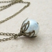 White Bud necklace: dainty, glass pearl pendant with leafy bronze-coloured caps