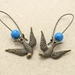 Swooping Swallow earrings: antiqued-brass coloured swallow charms with sky blue beads on long ear-wires