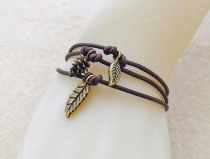 Set of three stackable, dark brown, faux leather bracelets with antiqued-brass leaf and pinecone charms
