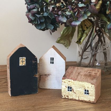 Little dwellings made from recycled wood. Highlights of gold leaf.