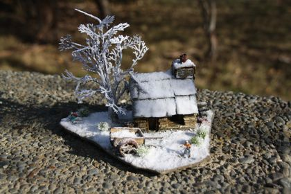 Miniature Stone Cottage with Old Relic's snow effect, featuring winter tree, two snowboarders and cart